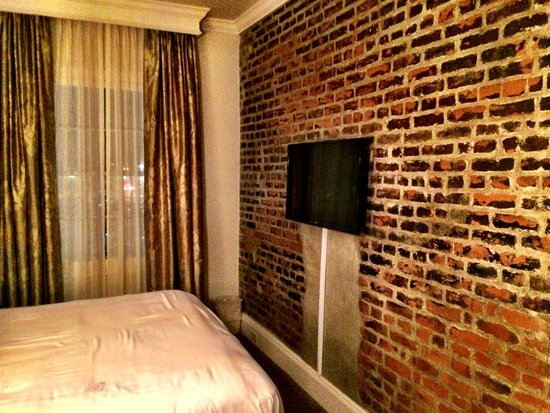 French Market Inn: exposed brick wall and flat screen tv