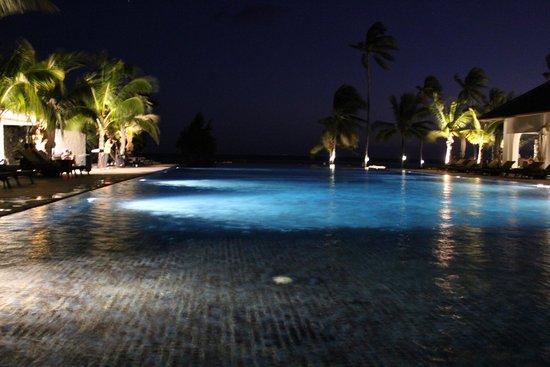 The Residence Zanzibar: Piscina del hotel con vistas a la playa por la noche