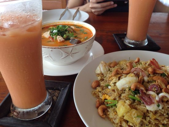 Poo Nurntong Restaurant: Pineapple rice in the foreground. Seafood Tom yum in the backdrop and Thai ice milk tea by the s