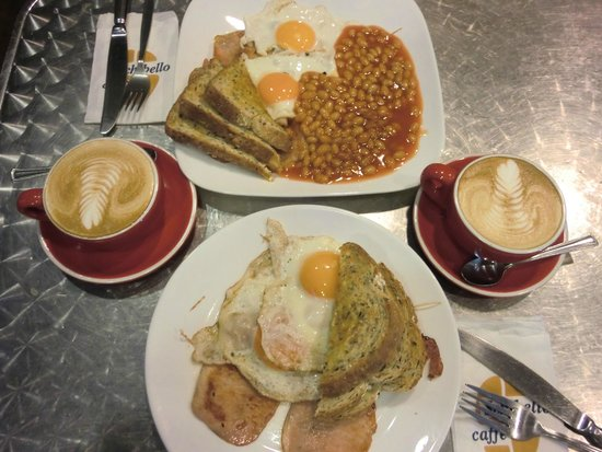 G'Day Cafe: G'day breakfast, plate on top comes with the lot; see the beautiful leaf design on the flat whit