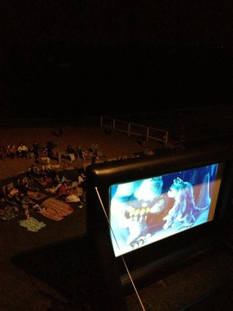 Madison Beach Hotel: Looking down at movie night on the beach from our balcony at the MBH.
