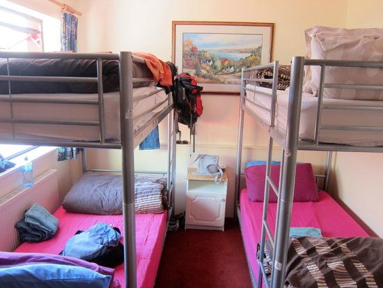 The Hideout Hostel: Four bed female dorm.  I'm standing where you put suitcases. Note the light!