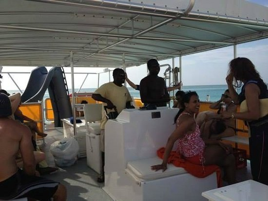 Caicos Dream Tours : Our guides driving the boat-- notice the slide on the boat!