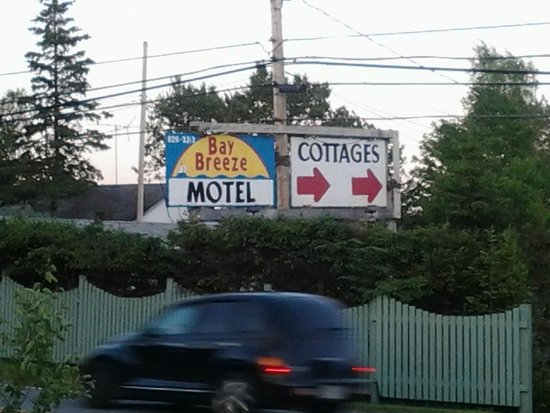Bay Breeze Motel and Cottages: Street View. Sign is not impressive. Oh, yes across the street was a OLD historic Church/Graveya