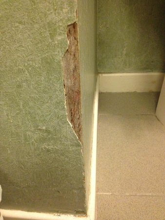 A-Haven Townhouse Hotel : Chunks of plaster missing from wall.