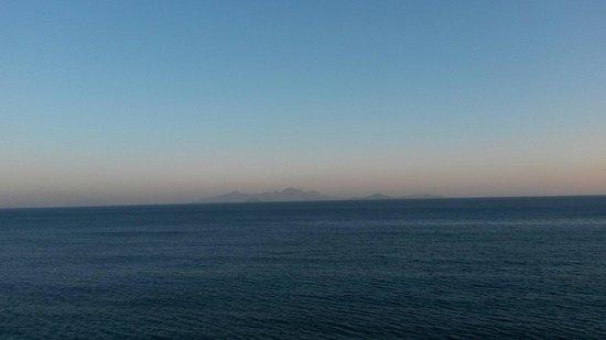 Mitsis Summer Palace: Sådan ser det klare blå vand og bjergene i horisonten ud. (Fra stranden om aftenen)
