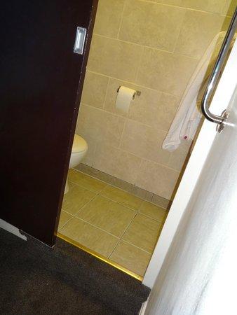 The Strand Hotel: narrow toilet area with sliding door