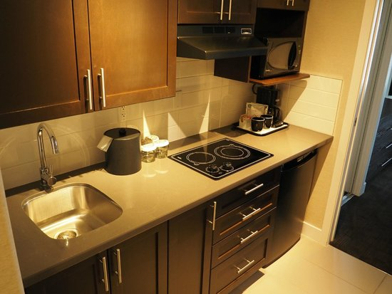 Sandman Signature Prince George Hotel: Kitchenette includes induction cooktop, microwave, fridge, and bar sink