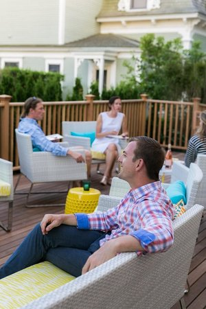 Guests lounging on outdoor deck at 21 Broad hotel, Nantucket