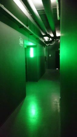 NYX Prague: corridor outside rooms, all black walls and green light