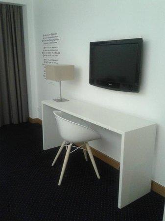Tryp Coimbra Hotel : Uma mesa de trabalho, a TV e o poema