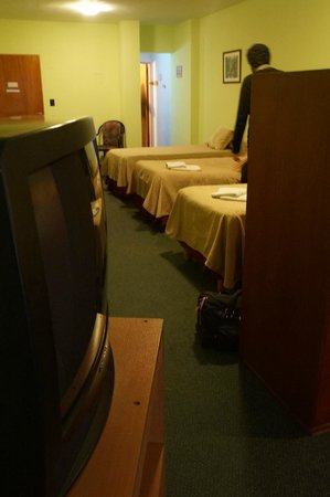 Fiamingo Apart Hotel : Vista a partir da cama de casal: TV, separação do ambiente por armário, e três camas de solteiro
