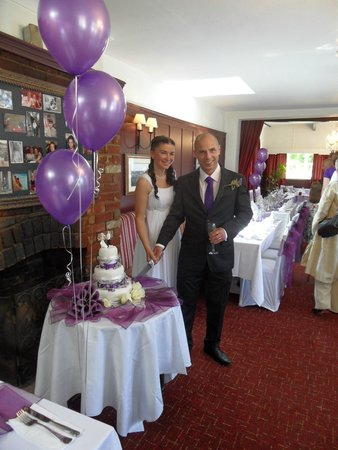 The Woolpack Elstead: Bride and groom cutting cake in restaurant