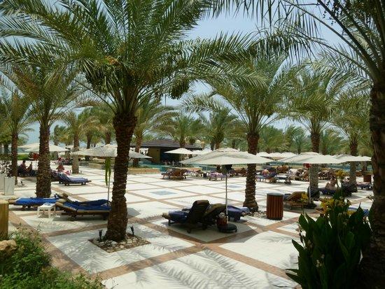 Hilton Ras Al Khaimah Resort & Spa : leżaki i parasole tuż przy barze w basenie.