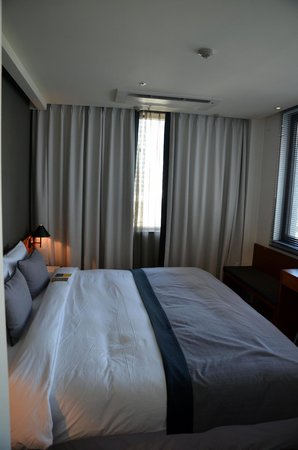Hotel ShinShin: King size bed with corner windows and small bench and desk
