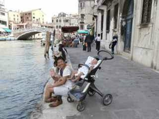 Cannaregio: Tourists dangling their feet in the canal whilst baby sleeps