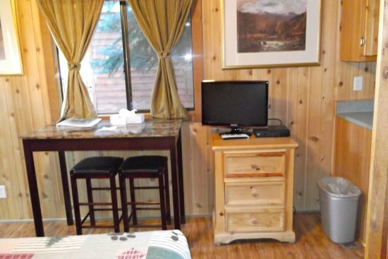 Lake View Lodge: sitting on bed, looking toward small TV, table and stools Cozy Cabin #9