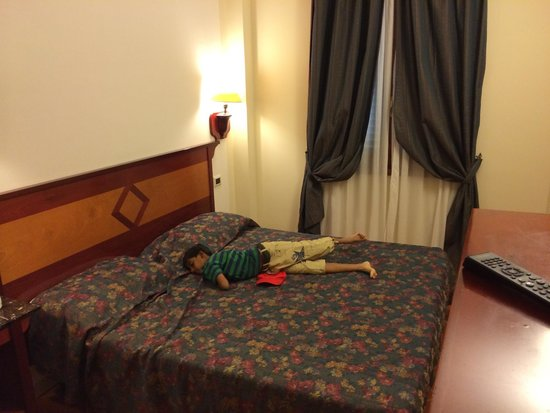 Hotel Corona D'Italia: My 9 year old relaxing in the bed. Gives you an idea of the double bed and the room size.