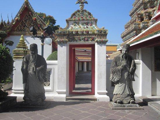 Wat Pho (Tempel des liegenden Buddha): Deux statues gardent une porte vers une coure