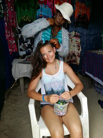 Royalton White Sands Resort: Sandra braiding our daughters hair at the shops on the beach