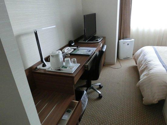 Vessel Inn Sapporo Nakajima Park : 机の上はそこそこ埋まっている。ベッドの向こうの細いスペースの奥に小さい椅子