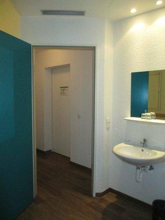 ibis Budget Berlin Ost: Blick in den Flur und auf das Waschbecken mit Spiegel