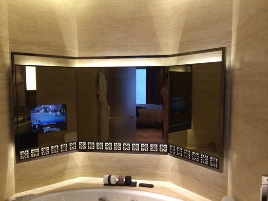 The Ritz-Carlton, Hong Kong : Bathtub with TV all wrapped in travertine marble.