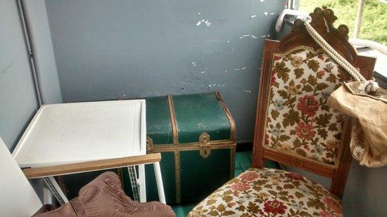 Hotel Sereno: Balconcino con baule decrepito contenente coperte, sedia imbottita