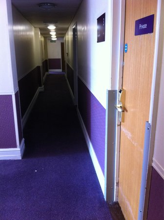 Premier Inn Newcastle Quayside: Purple hallway with damaged doors & trim in need of paint.