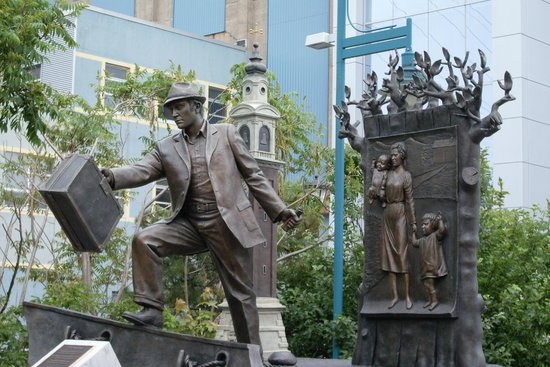 Halifax Waterfront Boardwalk: Pier 21 Statue of Immigrant Father heading to Canada