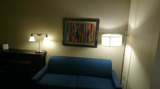 Holiday Inn Express & Suites: Sitting area with sofa bed and desk with executive chair.