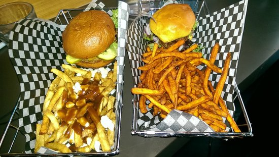 Eddie Burger & Bar : elk burger on the left with poutine, bison buger with sweet potato fries on right