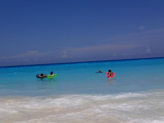 Crown Paradise Club Cancun: My girls floating in the ocean with their floaties