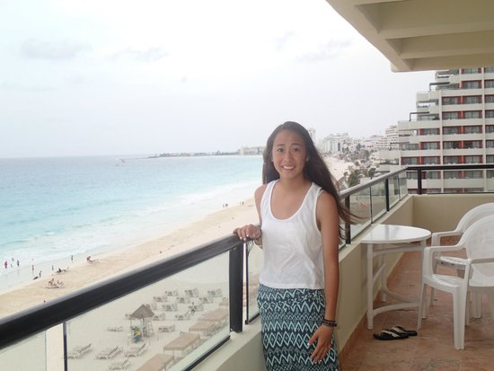 Crown Paradise Club Cancun: My daughter on our oceanfront wrap around balcony!