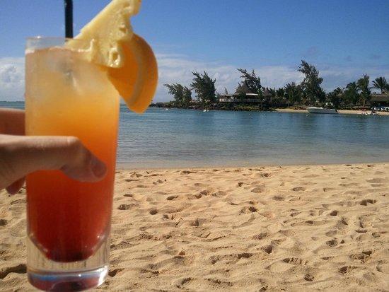 LUX* Grand Gaube : Cocktail sur la plage avec vue sur l'un des restos et la base nautique!!