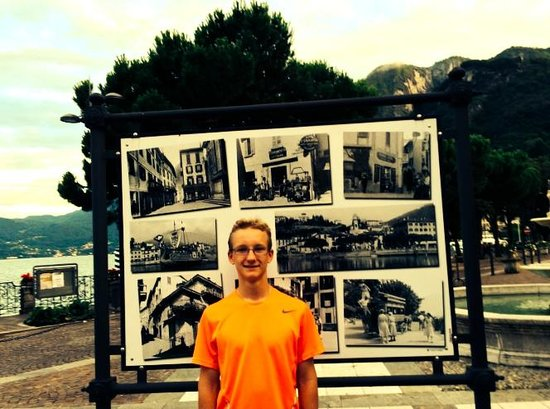 My son standing in front of the sign explaining some of the history of Menaggio.