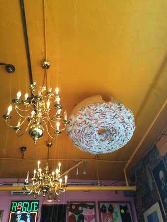 Voodoo Doughnut: Doughnut on the ceiling next to the chandelier.