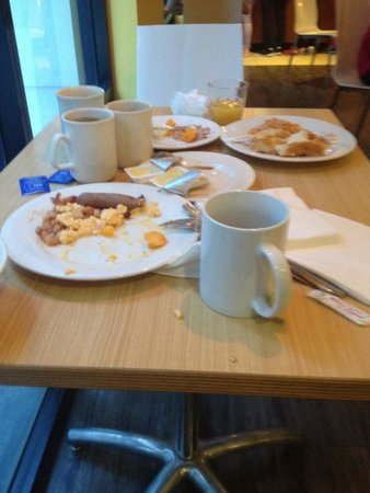Travelodge Hotel Sydney : Breakfast table stacked with dirty dishes - guests were coming and leaving more on the table whi
