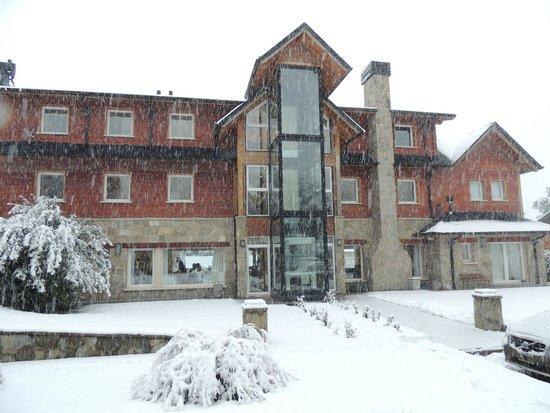Alma Andina Hosteria : Parte trasera vista desde el estacionamiento en plena nevada
