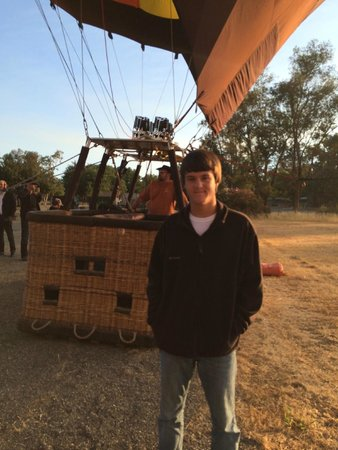 Balloons Above the Valley: My son as we are about to board, you can see the foot holes you have to climb to get in the bask