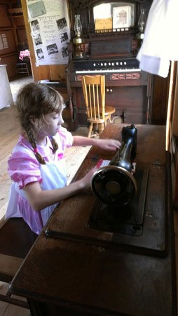 Ingalls Homestead - Laura's Living Prairie: Using the pedal sewing machine, with the organ behind.