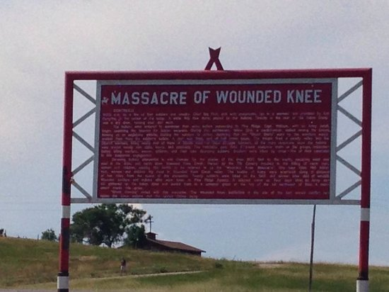 Wounded Knee Massacre Monument: Back of the sign with burial mound to the left