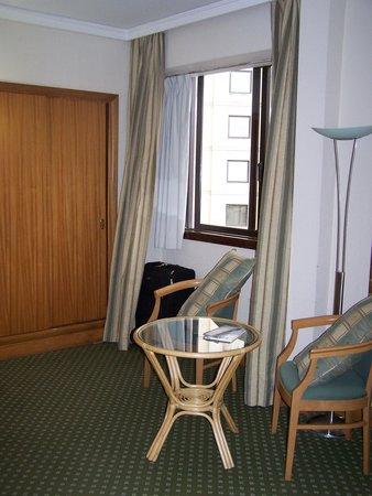 Hotel Mundial: Sitzecke mit Tisch, im Hintergrund der Schrank