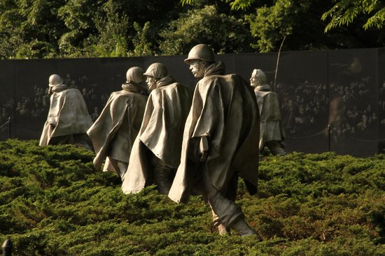 Korean War Veterans Memorial: View of soldiers on patrol wearing ponchos w grantite wall behind