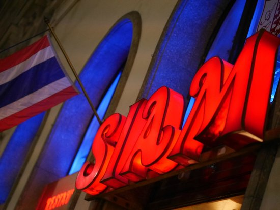 """Bright Neon Sign out front welcoming you to """"Siam"""""""