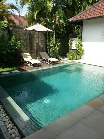 Disini Luxury Spa Villas : deck chairs and the pool. lovely waterfall behind the chairs