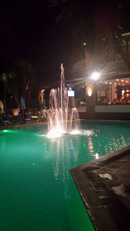 Legends Apartments: Fountain in pool at night