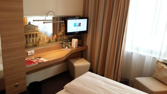 H4 Hotel Berlin Alexanderplatz: desk and tv area in front of the bed