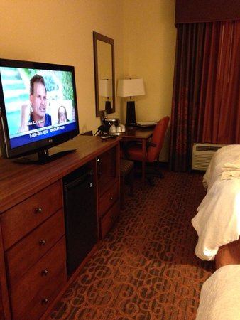 Hampton Inn & Suites Williston : Fridge and microwave within tv area. Two chairs by. Desk area