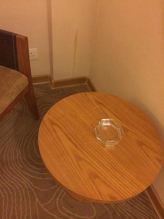 """Golden Tulip Al Jubail : Accent table with ashtray for """"non-smoking"""" room.  Unidentified stain on wall."""
